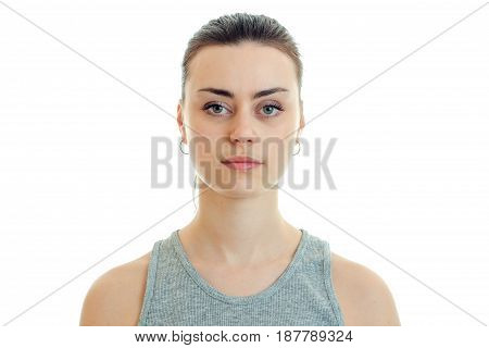 Portrait of beautiful serious girl who stands up straight and looking at camera isolated on white background