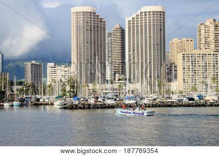 Honolulu Hawaii USA - May 30 2016: Yachts docked at Ala Wai Boat Harbour in the Kahanamoku Lagoon against cityscape of Ala Moana.