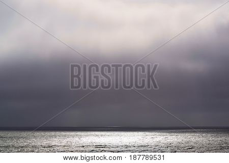 Low clouds and fog with sunrays shinning on the Pacific Ocean at the California Coast