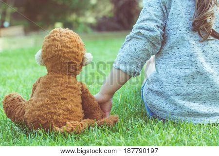 Little Girl Holding Soft Toy In The Garden