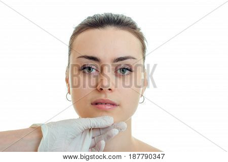 Portrait of beautiful serious girl without makeup that looks directly at the doctor close-up isolated on white background