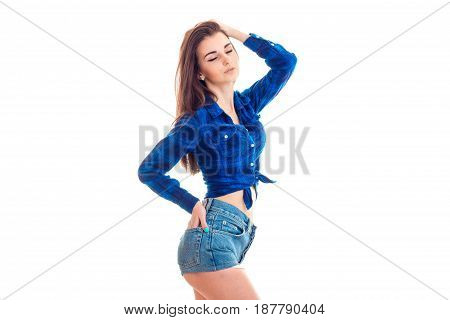 a charming young girl stands stretched back closing her eyes in shorts and blue shirt isolated on white background