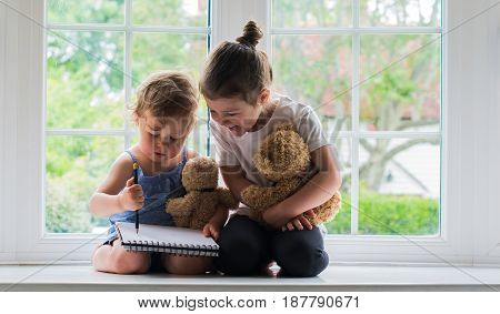 Two Little Girls Drawing On The Window