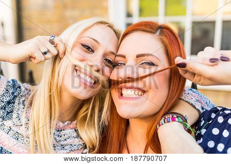 Girls making mustaches with hair. Happy and smiling young women playing with hair and pretending to have mustaches. Friendship and lifestyle concepts