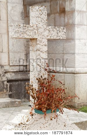 Cross from granite on a grave. At a foot of the cross the dried-up brown flowers