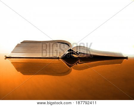 Book on desk with reflection in library