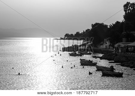 Port with fishing boats docked to the pier with sun peeking through the clouds. Black and white picture
