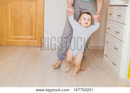Cute boy taking first steps holding mums hands