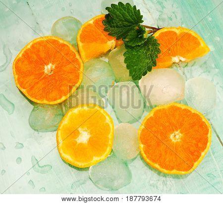 Fresh orange in ice cubes background. macro