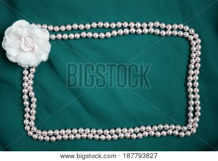 Indigo silk soft textile background with pearl beads frame with white rose in corner