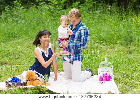 Happy young mother and father with their baby daughter relaxing on a blanket in a park celebrating with birthday cake.