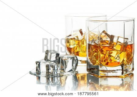 Two glasses of scotch whiskey with ice cubes on a white background.