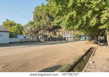 NIEU BETHESDA SOUTH AFRICA - MARCH 22 2017: Early morning street scene showing an irrigation canal in Nieu-Bethesda an historic village in the Eastern Cape Province. The church was built in 1905