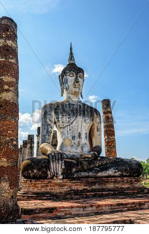 Ancient Buddha statue sitting among the ruins under the bright sky of Wat Maha That temple in Sukhothai Historical Park is an old city and famous tourist attraction of Sukhothai Province Thailand