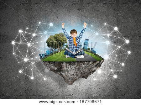 Connection concept floating island and happy kid boy with book sitting on it