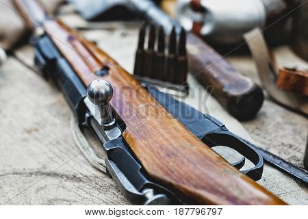 Rifle and cartridges on fabric with shallow depth of field