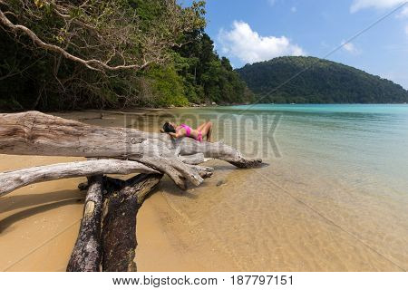 Woman relaxing, lying on a dead tree trunk at the Mu Ko Surin Maritime park, Thailand