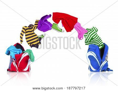 Colorful clothing fly out of backpack and falls into another backpack on white background