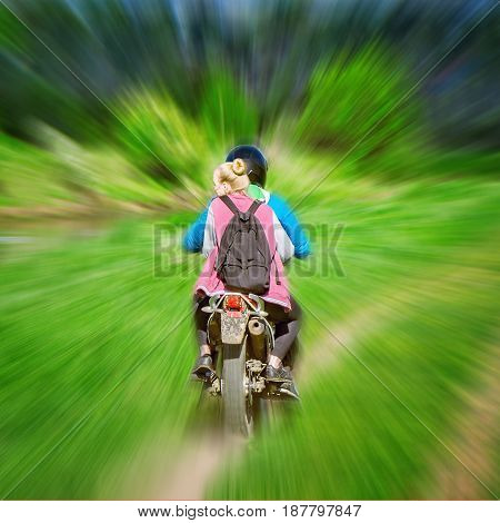 Young woman and man move fast on the bike.