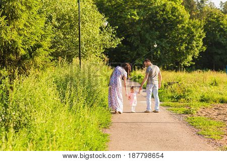 family, parenthood and people concept - happy mother, father and little girl walking in summer park.