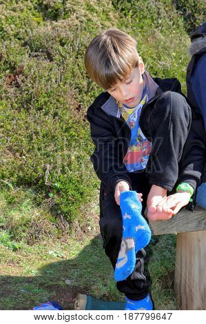 Cornwall, Uk - April 2 2017: Young Boy Examines His Feet While Out Walking