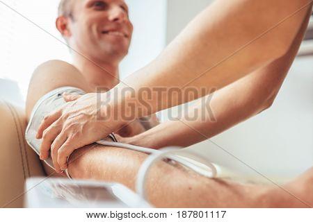 Nurse measures man's blood pressure with a blood pressure meter