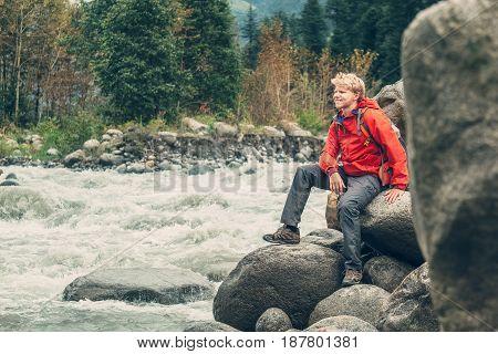 Young man tourist sits rocky mountain river bank