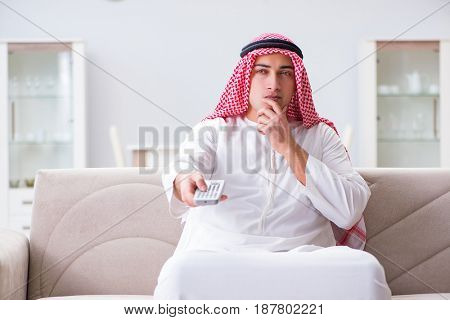 Arab man watching tv at home