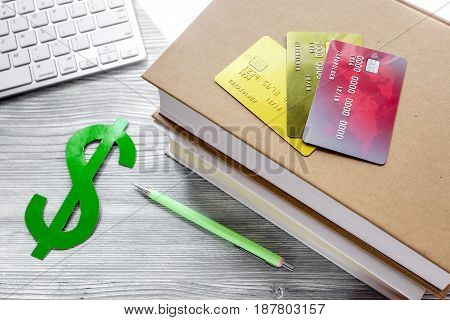fee-paying education set with dollar sign, books and creit cards on light wooden table background