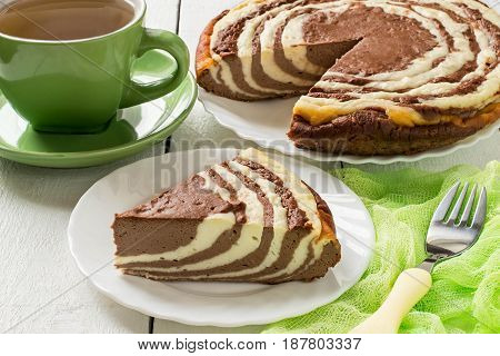 Delicious homemade chocolate cake with cottage cheese Zebra (Marble cake). Tasty breakfast. Piece is cut from cake green cup of tea and green gauze textiles on white wooden table. Selective focus