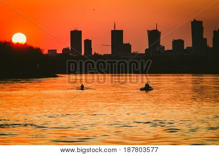 Canoeists on Vistula river nad sunset over Warsaw city