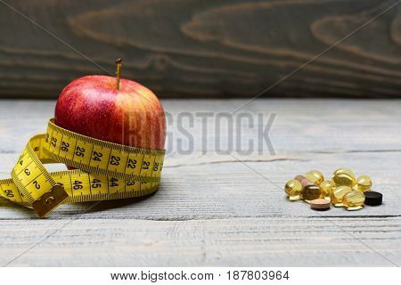 Pills And Red Apple Belted Around With Measuring Tape