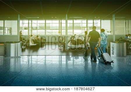 FRANKFURT GERMANY - JUL 3 2015: Interior of Frankfurt airport with family senior people waiting for their airline walking with trolley luggage delayed flight or plane arrival departure
