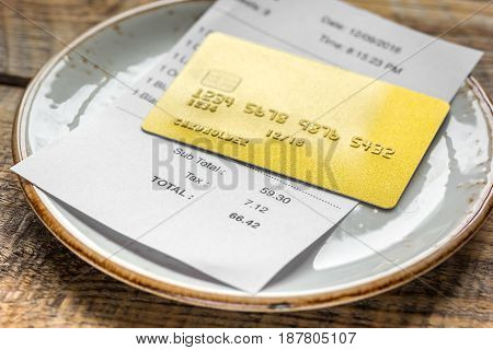 credit card for paying, plate, glasses and check on cafe wooden desk background