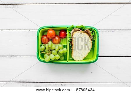school lunch set with sandwich and vegetables in lunchbox on white wooden table background top view