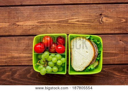 homemade lunch with cherry, grape and sandwich in green lunchbox on wooden table background top view mockup
