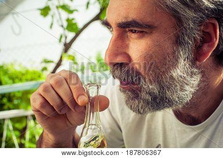 Bearded man drinking rakia brandy. Outdoor scene