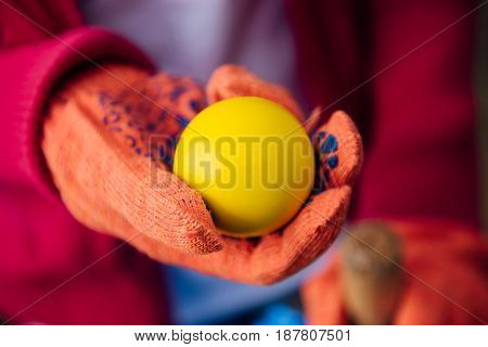 Abstract colorful background with a hand in glow holding a yellow ball. Shallow DOF