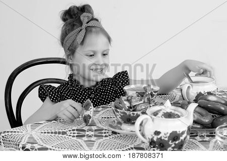 Beautiful little girl sitting at dining table and drinking tea.Black-and-white photo. Retro style.