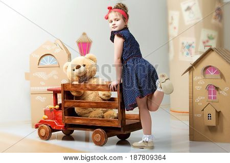 Cute little girl preschooler playing with a toy car in the house out of cardboard.