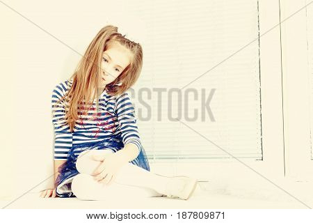 Little girl in blue striped dress and a white bow on her head.She sits at the window with sad eyes something lost in thought.Creative toning of a photograph.