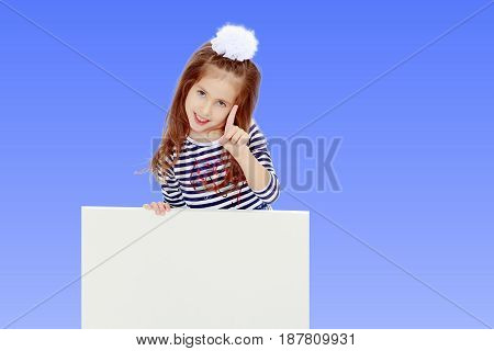 The little blonde girl with long hair and with a white bow on her head , in a blue striped summer dress.She peeks out from behind white banner, and a threatening finger.On the pale blue background.