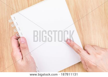Close Up Hand Holding And Point At Empty White Open Book Above Wood Desk ,mock Up Template For Addin