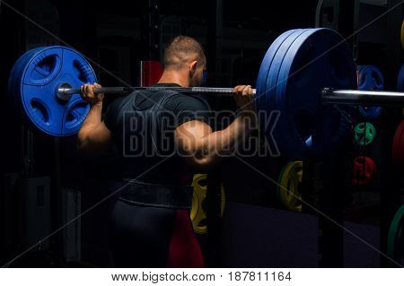 Professional Athlete Stands With A Barbell On His Shoulders