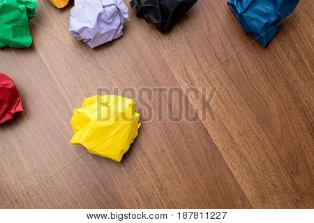 Top View Of Yellow Crumpled Paper Ball On Dark Brown Wood Table With Group Of Colorful Crumpled Pape