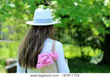 Female in white summer fashion carries pink flowers in shoulder bag