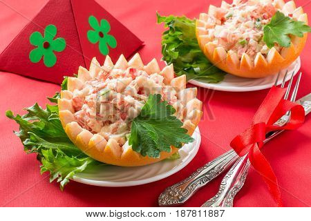Original festive salad with grapefruit and crabmeat. Served in cups from grapefruit peel. Idea of festive snack for Valentine's Day Mother's Day birthday. Red shades in decoration. Selective focus