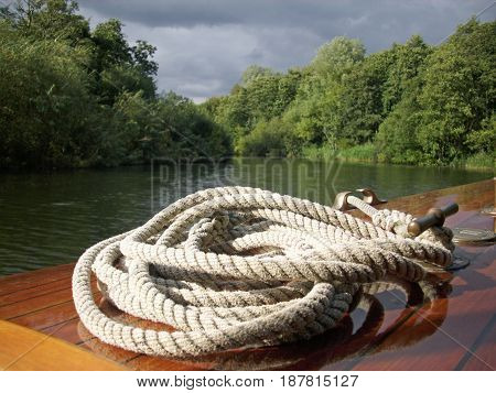 Wooden boat on one of the Norfolk Broads. Rope coiled on the highly polished bow. Surrounded by trees with grey blue sky.