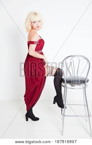 Portrait of an attractive blonde girl in a red dress on a white background.