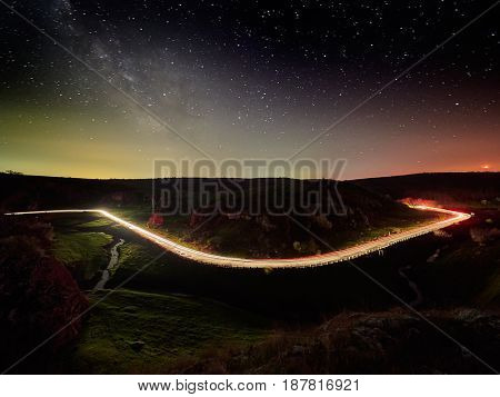 Night sky with milky way and stars, night road illuminated by car's light trails - Cheile Dobrogei, Romania
